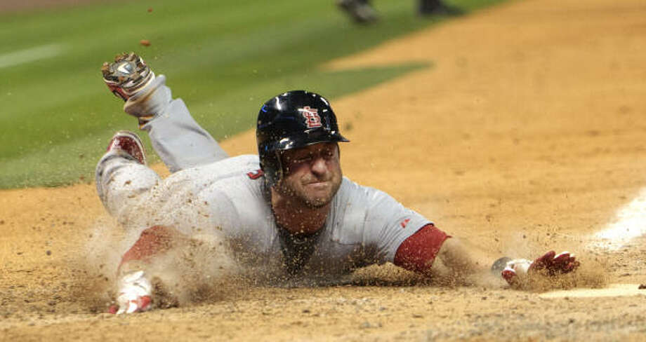 Cardinals' Nick Punto slides into home in the seventh inning. Photo: Bob Levey, Getty Images