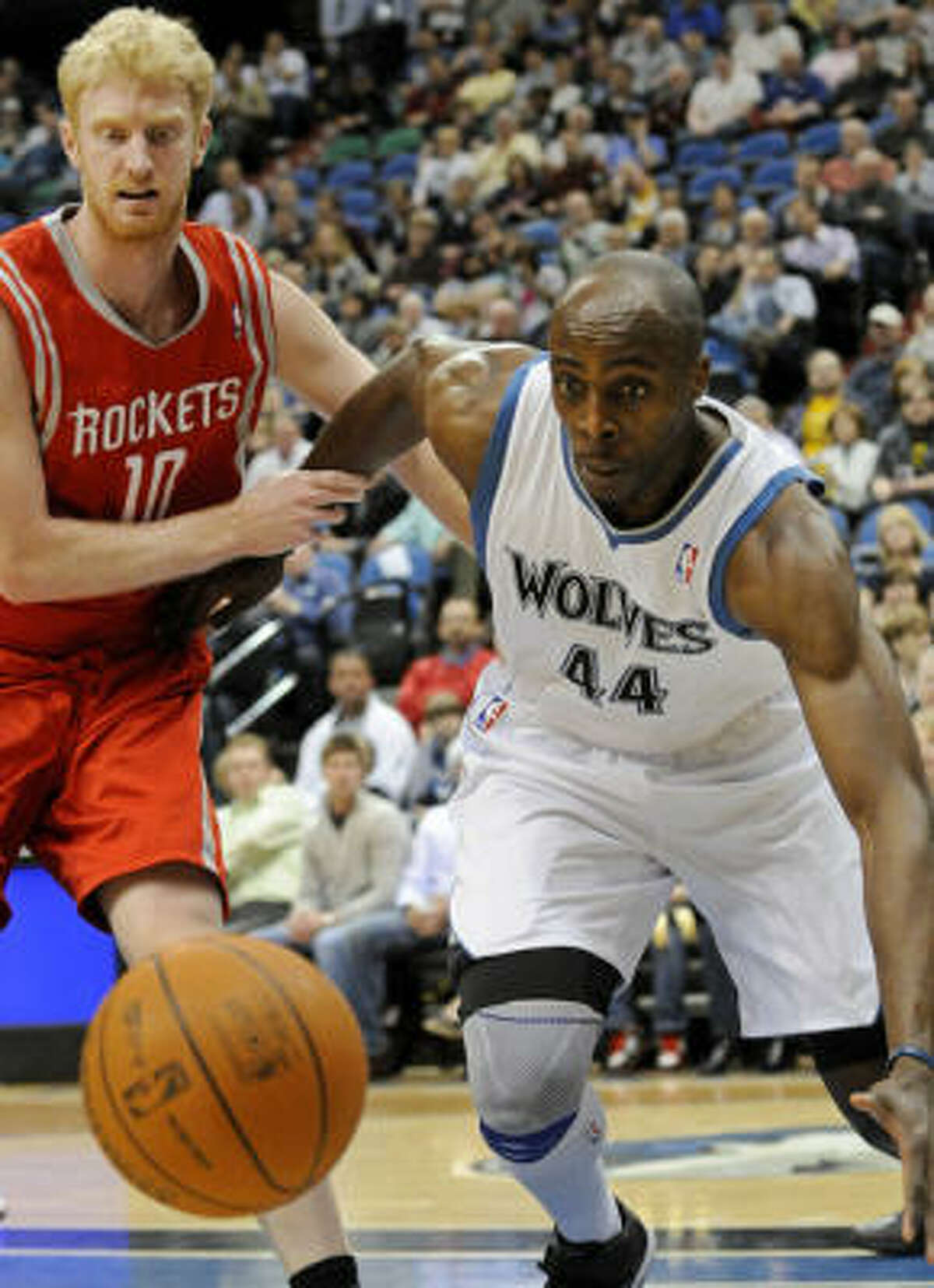 Rockets forward Chase Budinger, left, tries to hold back Timberwolves' Anthony Tolliver as he races for the loose ball.