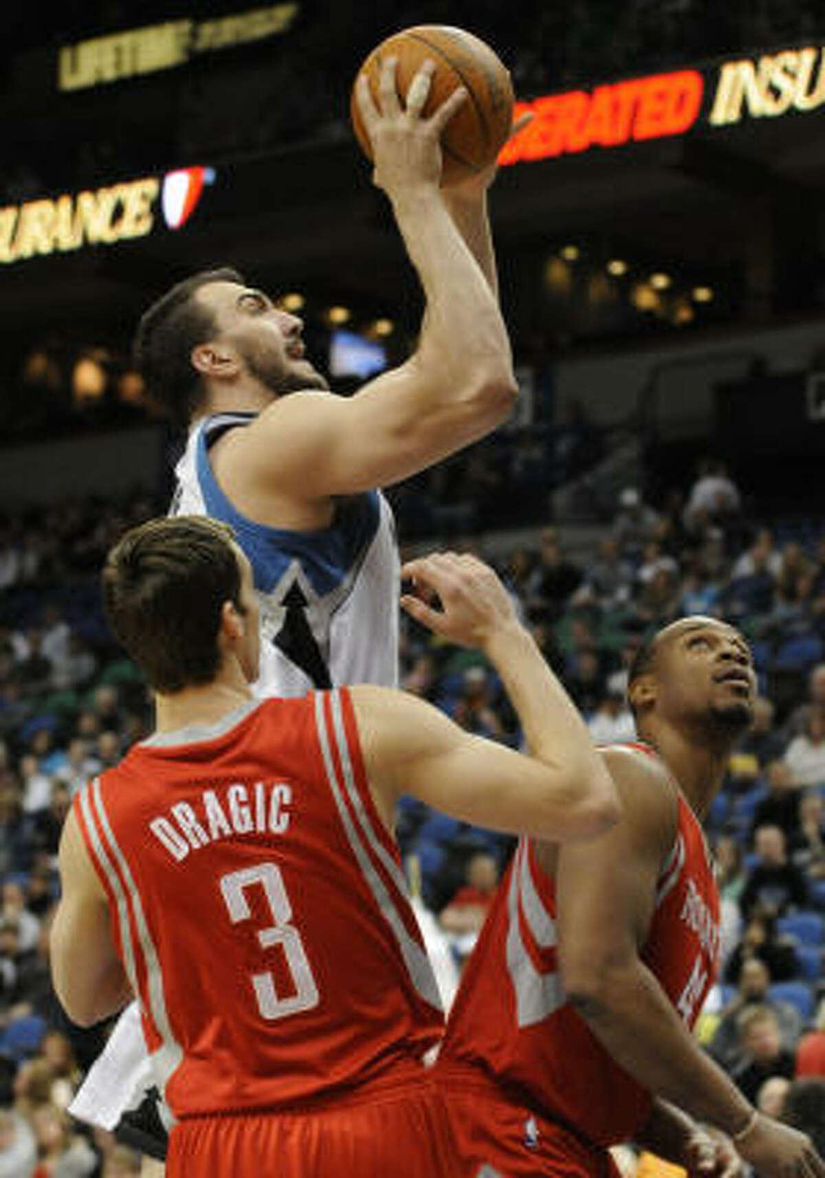 Timberwolves' Nikola Pekovic, center, shoots as Rockets' Goran Dragic (3) and Chuck Hayes, right, watch.