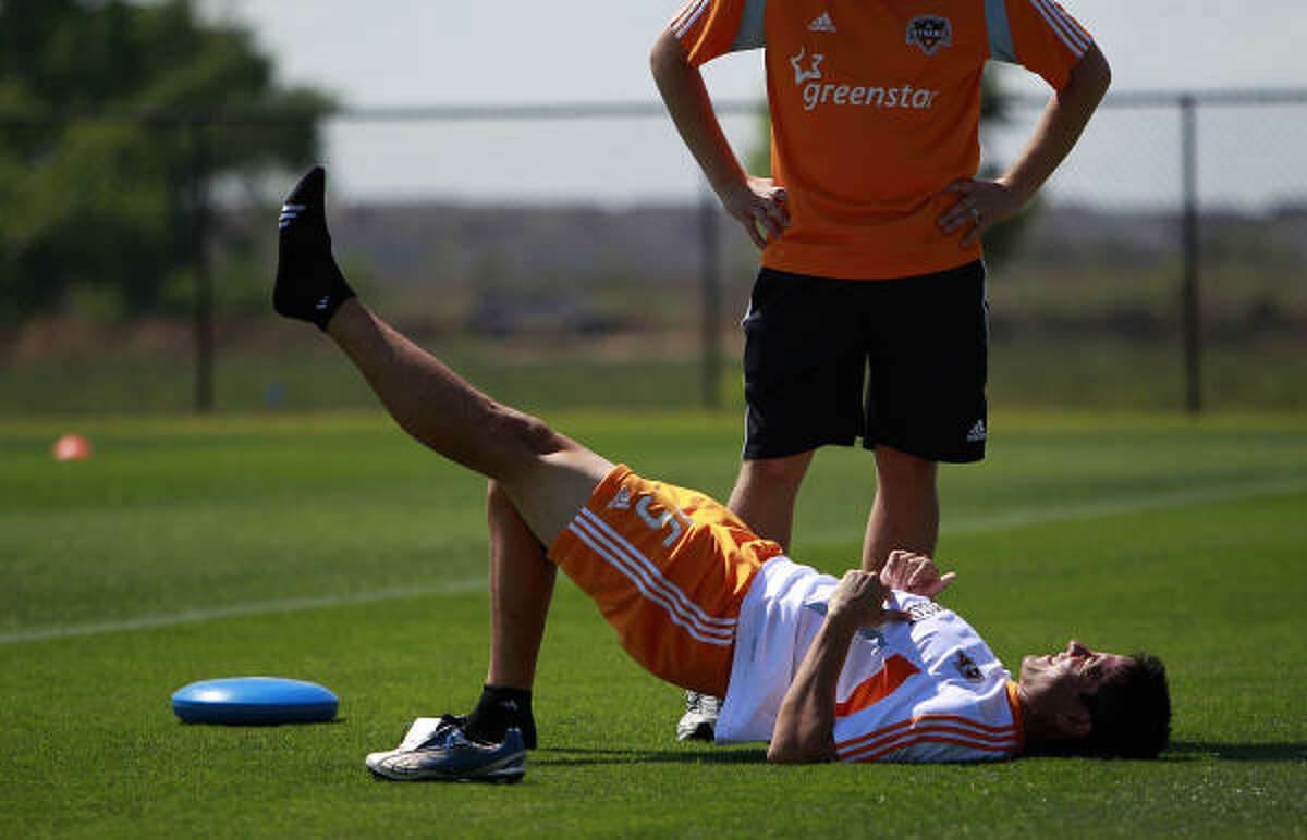 Dynamo forward Brian Ching stretches before the first practice at the new facility.