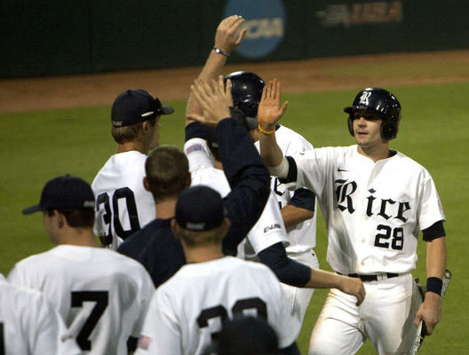 Rice catcher Geoff Perrott, right, is congratulated by teammates after scoring a run during the eighth inning. Photo: Cody Duty, Chronicle