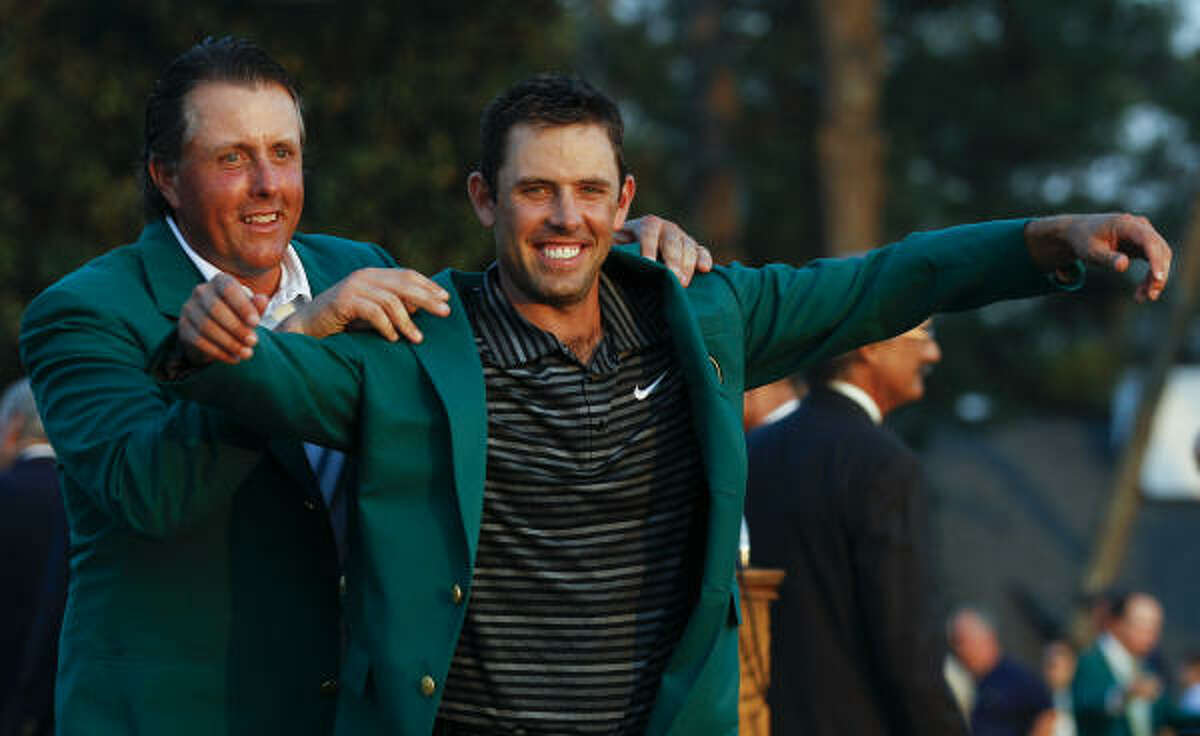 Former champion Phil Mickelson, back, helps Charl Schwartzel of South Africa with his green Masters jacket.