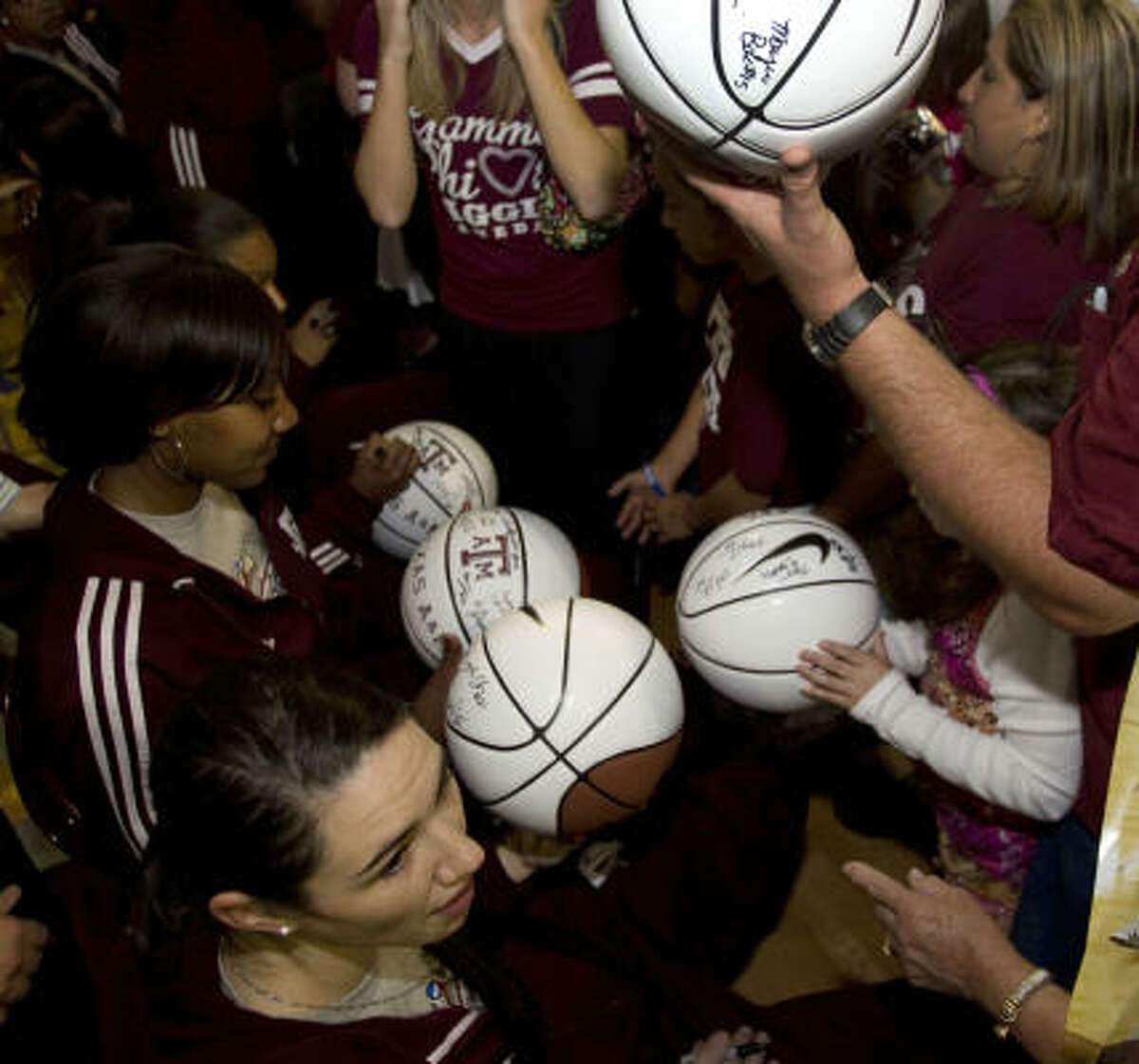 Texas A&M's Maryann Baker, lower left, signs autographs following the rally celebrating the Aggies' NCAA title.
