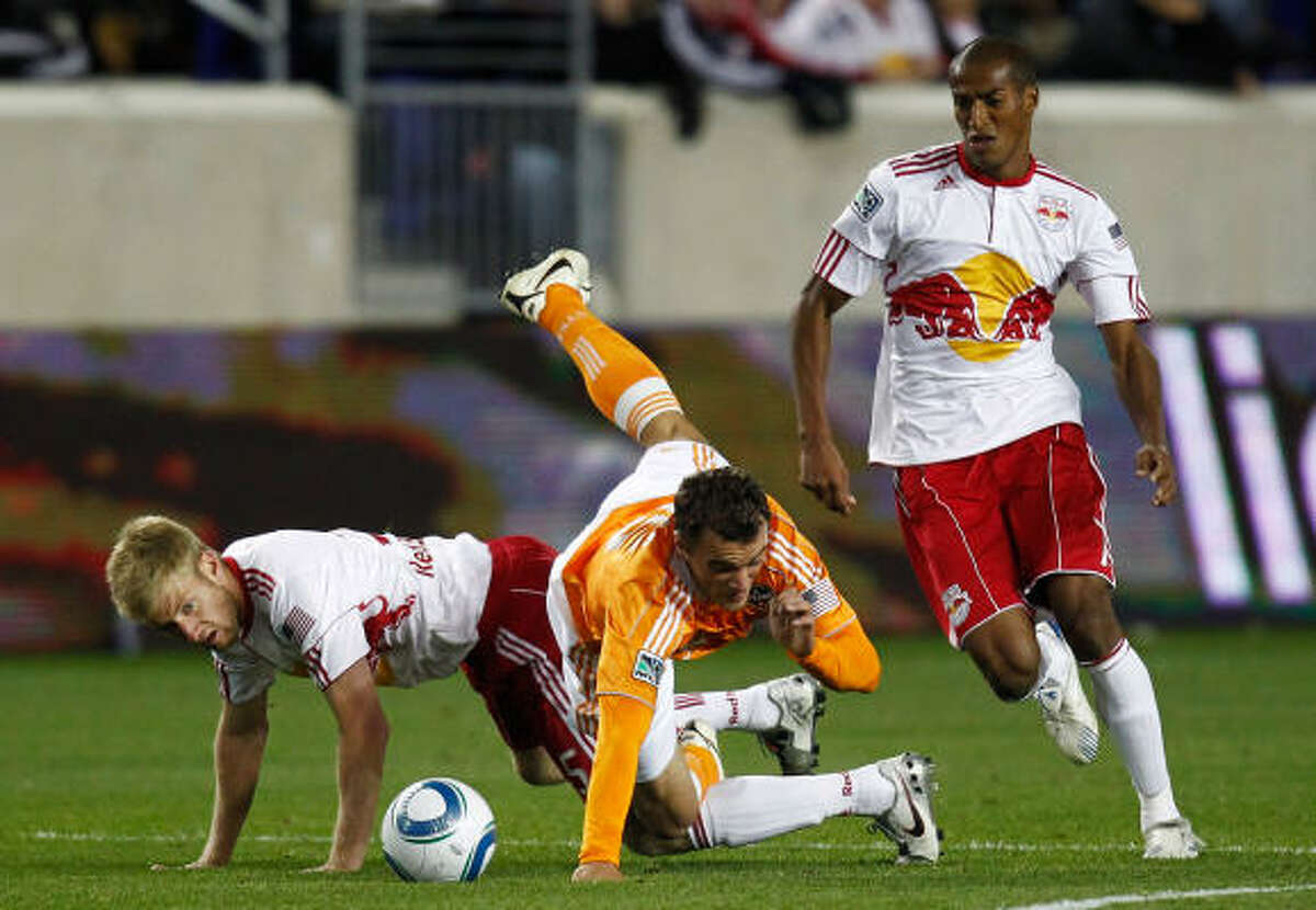 April 2: Dynamo 1, Red Bulls 1 Cameron Weaver of the Dynamo is tripped up by Tim Ream, left, and Roy Miller of the New York Red Bulls.