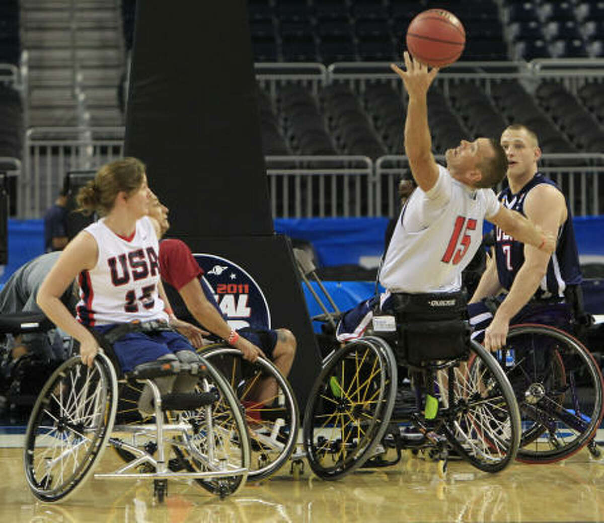 Jeff Glassbrenner (15), of Little Rock, Ark., reaches up to grab a rebound with teammate Carlee Hoffman, left, of Chicago.