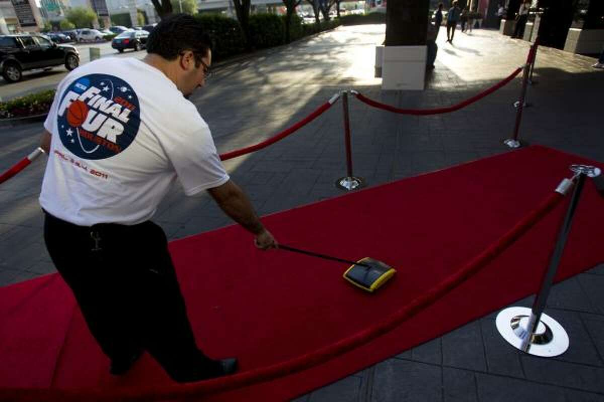 Ivo Pecheni, an employee at the Hotel Derek, cleans the red carpet before the arrival of the team.