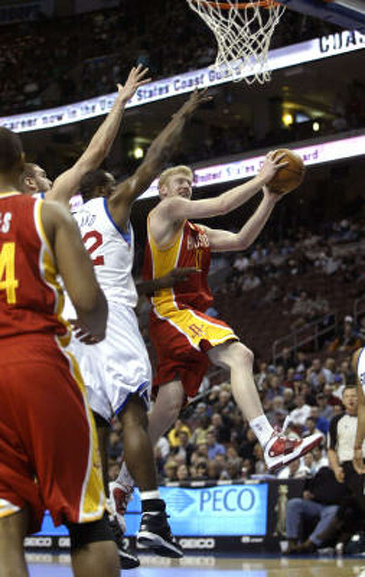 Rockets forward Chase Budinger, right, goes up for a score as 76ers' Elton Brand defends.