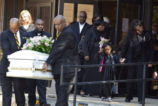 Emmanuel Kajoh, above the casket, and his wife Betty Ukera, far right, follow the casket of their daughter Elizabeth Kajoh after Elizabeth's funeral Saturday, March 5, 2011,  at St. Elizabeth Ann Seton Catholic Church in Houston. Elizabeth, 19-months old, was one of four children to die in a fire at Jackie's Child Care Feb 24, 2011. Photo: Nick De La Torre, Houston Chronicle