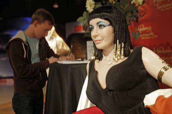 """A visitor signs a condolence book next to a figure of actress Elizabeth Taylor in her title role in the 1963 epic film, """"Cleopatra,"""" at Madame Tussauds Hollywood wax museum in Los Angeles."""