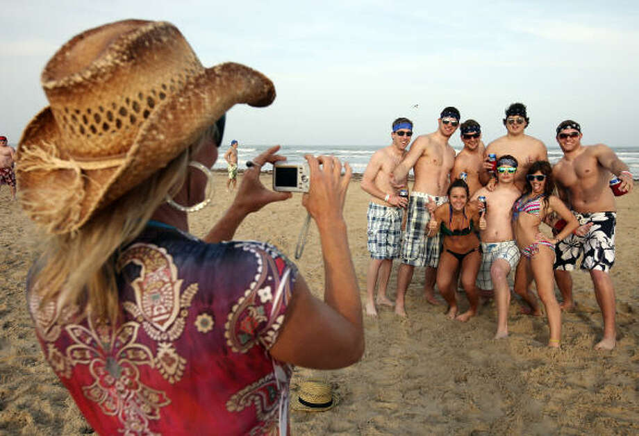 "Amy Ware, from Austin, photographs spring breakers Sunday March 13, 2011 during ""Texas Week""  on South Padre Island. Photo: EDWARD A. ORNELAS, SAN ANTONIO EXPRESS-NEWS"