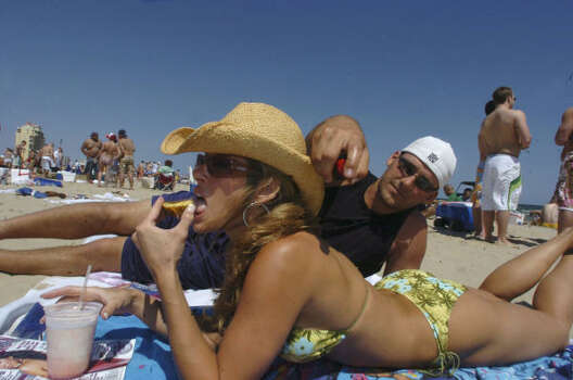 Crystal Stevenson, 22, from the University of Indiana, relaxes on the beach at South Padre Island while Tony Bickenstaff, 24, from Eastern Illinois University, applies sun tan oil on her during their spring break. Photo: BILLY CALZADA, SAN ANTONIO EXPRESS-NEWS