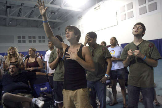 Zach Almond (front, center, arm raised) prays with other participants involved with Beach Reach at the convention center on South Padre Island during Spring Break 2007. Most of those involved in the faith-based effort are Baptist college students and come down to the island to encourage other partying students to accept Christ into their lives. Photo: JOHN DAVENPORT, SAN ANTONIO EXPRESS-NEWS