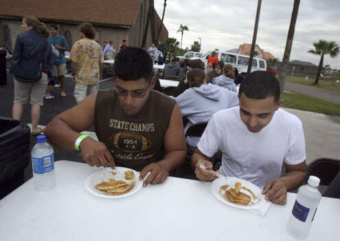 Hugo Munoz, left, and Brandon Watts enjoy a free pancake breakfast in the parking lot of the Island Baptist Church during Spring Break 2007 on South Padre Island. The mostly Baptist group offers free food and transportation in an effort to spread the word about their faith. Photo: JOHN DAVENPORT, SAN ANTONIO EXPRESS-NEWS