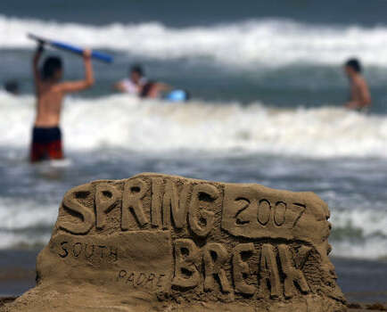 Kids play in the surf on South Padre Island during Spring Break 2007. The sand sculpture was made by Christopher Hahn of Austin, Texas who was visiting the beach with his family. Photo: JOHN DAVENPORT, SAN ANTONIO EXPRESS-NEWS