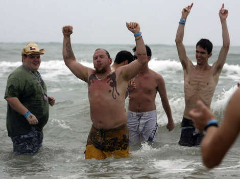Jeremy Oster (center, tattoos) raises his arms while celebrating his baptism in the Gulf of Mexico during Spring Break on March 15, 2007. Oster was there with a group of mostly Baptist students called Beach Reach. Photo: JOHN DAVENPORT, SAN ANTONIO EXPRESS-NEWS