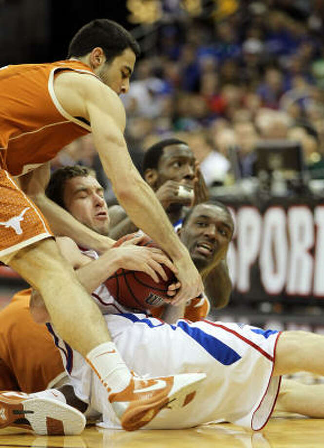 Kansas' Brady Morningstar fights for possesion with Dogus Balbay (4) and Jordan Hamilton (3) of the Texas Longhorns. Photo: Jamie Squire, Getty Images
