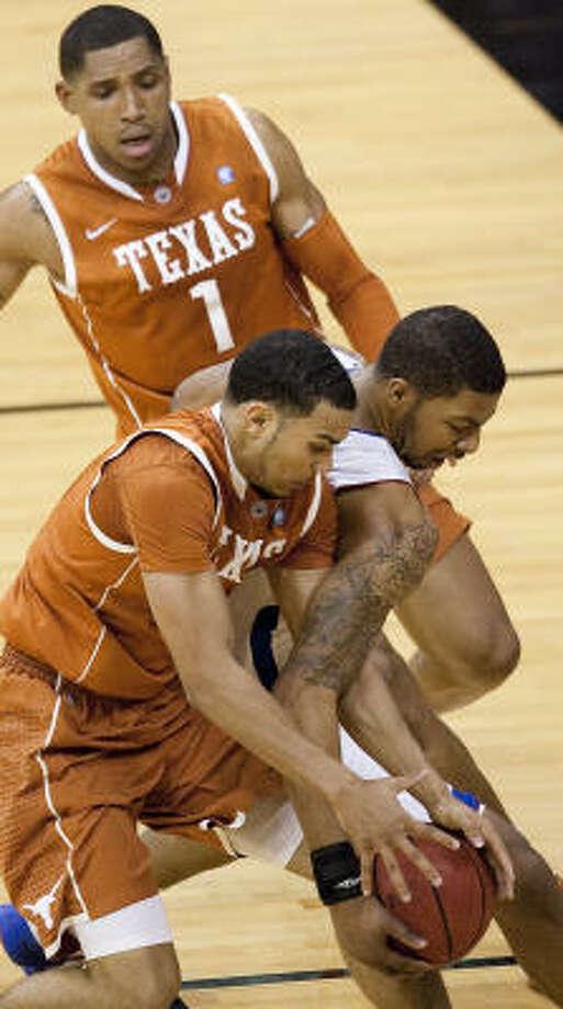 Texas' Cory Joseph, left, and Kansas' Markieff Morris fight for a loose ball as Texas' Gary Johnson (1) watches the play. Photo: Todd Feeback, MCT