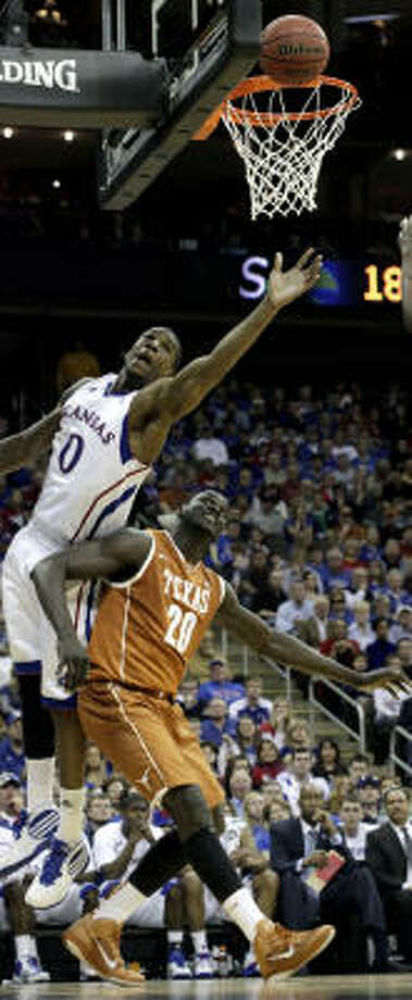 Kansas forward Thomas Robinson (0) gets around Texas forward/center Alexis Wangmene (20) to put up a shot. Photo: Charlie Riedel, AP