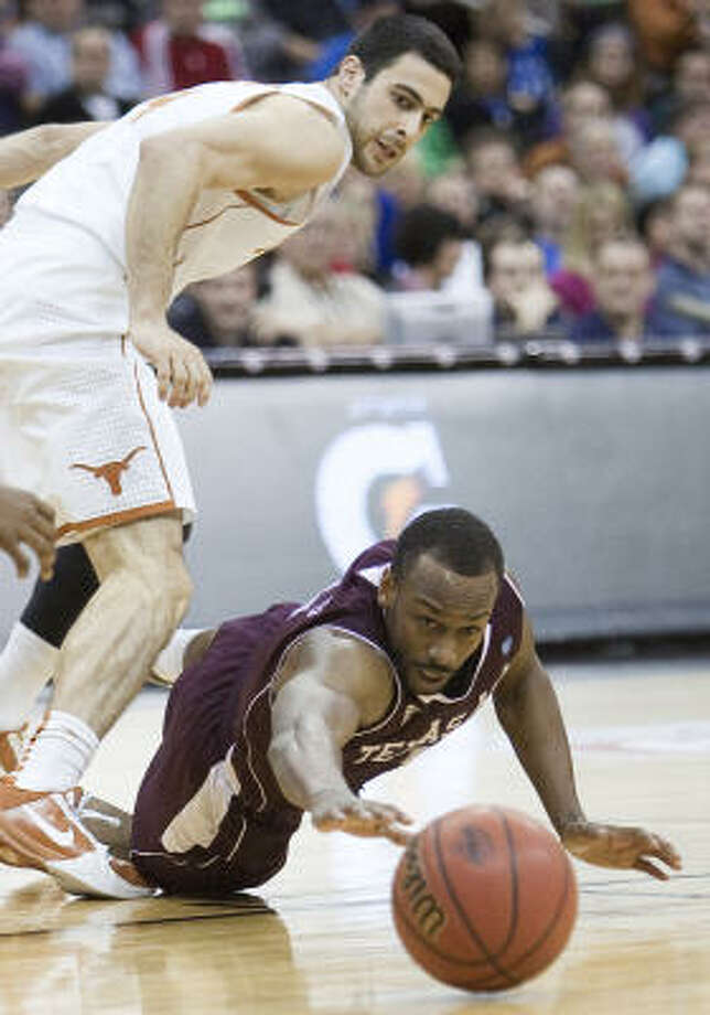 Texas A&M's Dash Harris hits the deck for a loose ball as Texas' Dogus Balbay watches the play. Photo: Rich Sugg, MCT