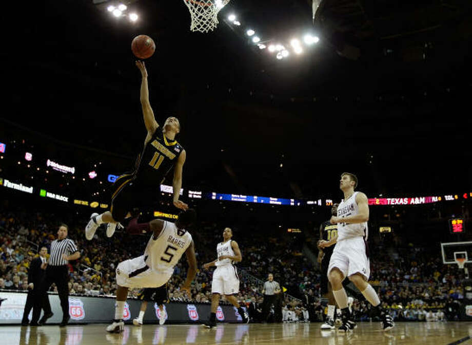 Missouri's Michael Dixon looks to lay the ball in the basket as A&M's Dash Harris defends. Photo: Jamie Squire, Getty Images