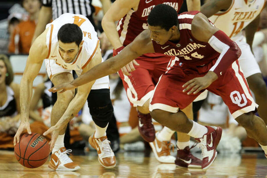 Texas guard Dogus Balbay grabs the ball as Oklahoma's Carl Blair looks to steal it. Photo: Jamie Squire, Getty Images