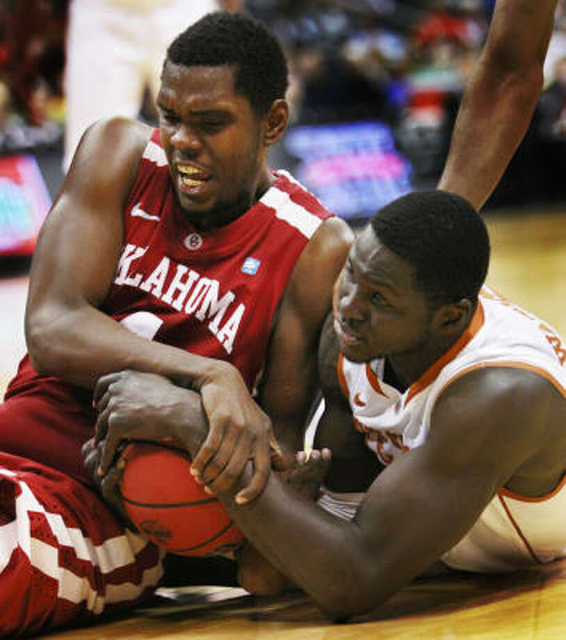 Oklahoma forward Andrew Fitzgerald, left, and Texas forward Alexis Wangmene battle for a loose ball during the first half. Photo: Orlin Wagner, AP