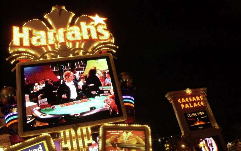 Harrah's casino and and Caesars Palace are shown in Las Vegas on Wednesday night, July 14, 2004. Harrah's Entertainment Inc. took the gambling industry by surprise after agreeing to buy Caesars Entertainment Inc. for more than $5 billion in cash and stock, according to a person familiar with the negotiations. The deal eclipses last month's high-profile MGM Mirage merger with Mandalay Resort Group and creates the largest gambling company in the world while setting up a key battle for customers on the lucrative Las Vegas Strip. (AP Photo/Isaac Brekken) Photo: ISAAC BREKKKEN, Hearst / AP