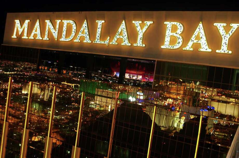 "The Las Vegas Blvd. ""strip"" is seen reflected in one of the towers of the Mandalay Bay Resort Hotel & Casino Saturday, Dec. 4, 2004. The new nightclub, Mix,  is seen inside on the top floor, center. Mix will be one oof the best places to watch the New Year's fireworks show in Las Vegas.  (AP Photo/Eric Jamison) Photo: EIRC JAMISON, Hearst / AP"