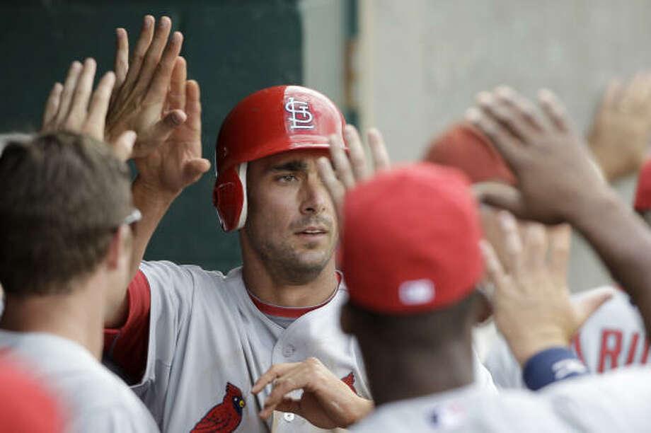 Cardinals third baseman Matt Carpenter is congratulated by teammates after scoring during the second inning. Photo: David J. Phillip, AP