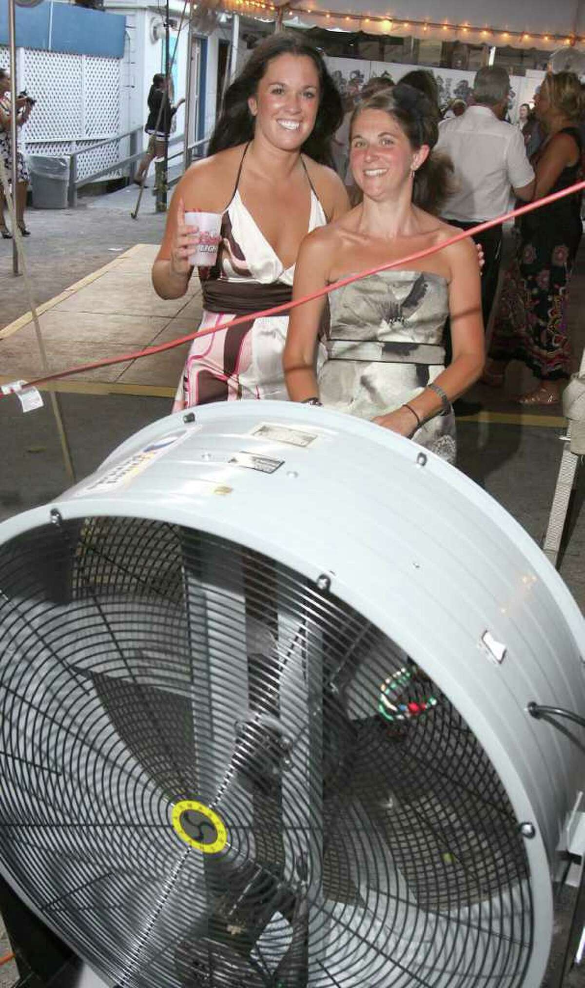 Saratoga Springs, NY - July 21, 2011 - (Photo by Joe Putrock/Special to the Times Union) - Lindsay Donina(left) and Tara Rinaldi(right) try to be the heat by standing in front of a fan during during the 18th Annual Earl B. Feiden Siro?'s Cup to benefit the Center for Disability Services Foundation.
