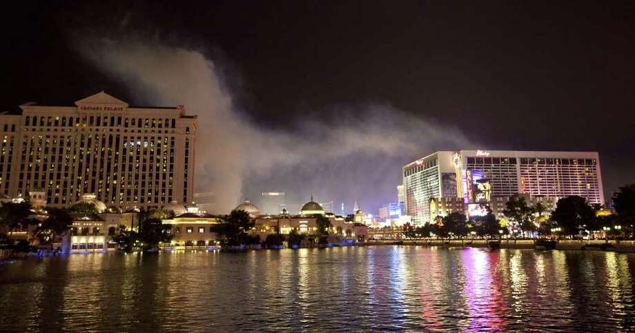 Smoke from a fireworks show over Caesar's Palace begins to drift across The Strip to The Flamingo, Sunday, July 3, 2011, in Las Vegas.  (AP Photo/Julie Jacobson) Photo: Hearst