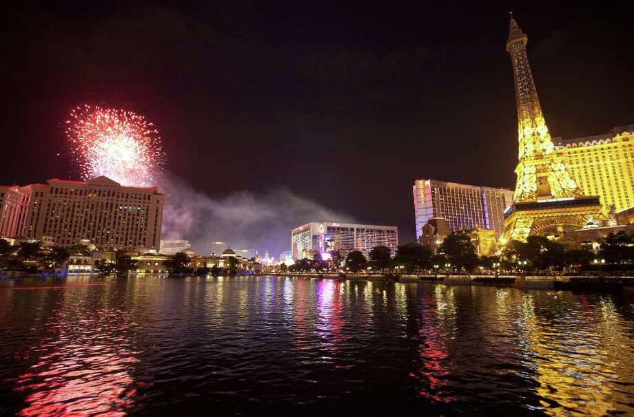 Light from Independence Day weekend fireworks is reflected in the water in front of the Bellagio Hotel as they explode over Caesar's Palace on The Strip, Sunday, July 3, 2011, in Las Vegas. (AP Photo/Julie Jacobson) Photo: Hearst
