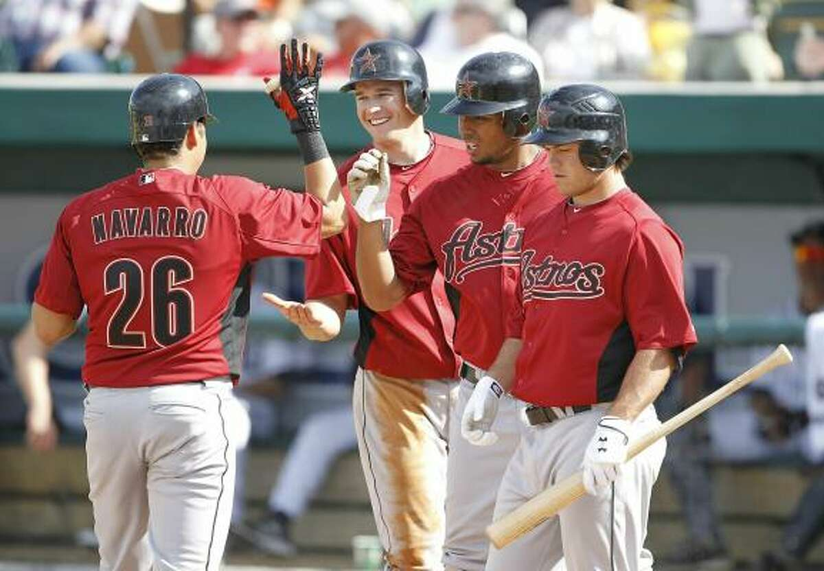 Oswaldo Navarro (26) celebrates with teammates (from right) Koby Clemens, Angel Sanchez and T. J Steele after hitting a three-run homer in the eighth inning.