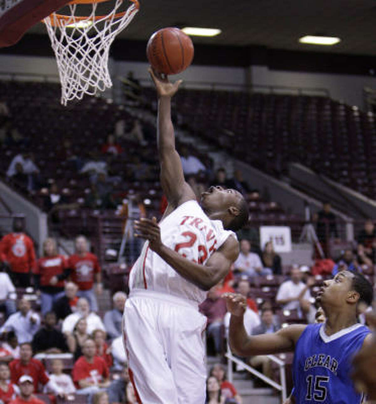 March 2: Travis 58, Clear Springs 46 Travis' Anthony Odunsi floats in for a layup over Clear Springs' Jeff Beverly during Wednesday's Class 5A Region III quarterfinal at the Campbell Center. Odunsi scored 15 points to help lead Travis to a win.