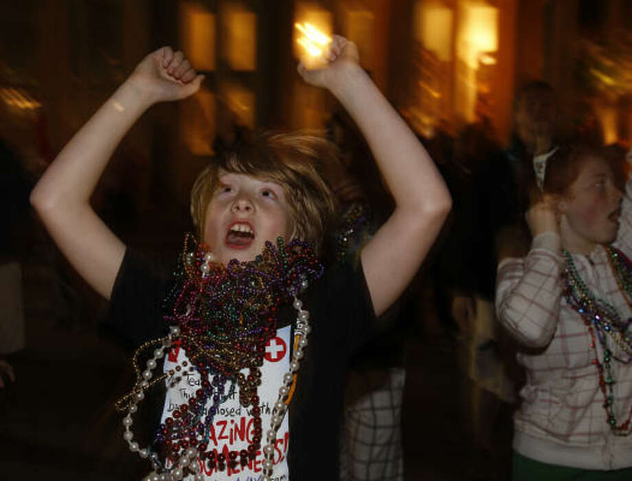 Brody Glover, 10, visiting from Saskatchewan, Canada tries to catch beads during the 100th celebration of Mardi Gras! Galveston along the Strand. Photo: Melissa Phillip, Houston Chronicle