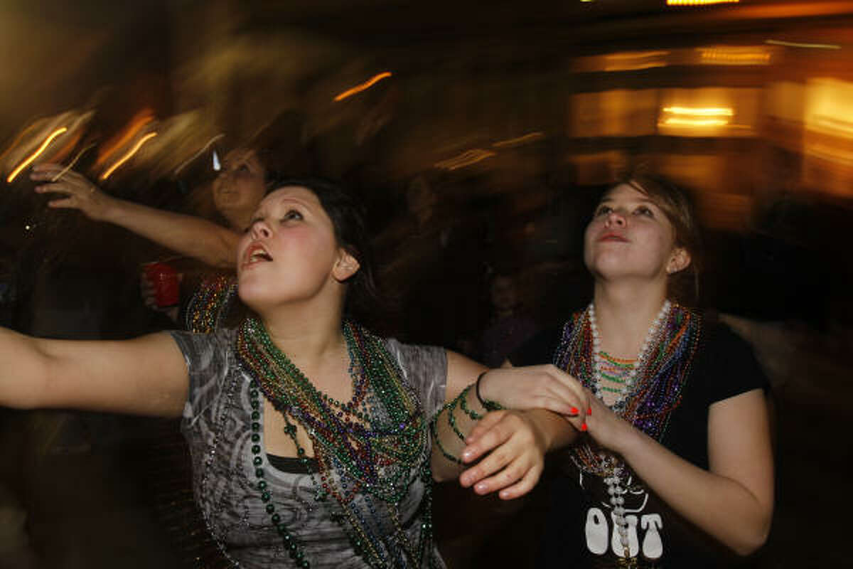 Elyssa Lara, left, and Maddie Nelson, right, both 15 and from Seabrook try to catch beads.