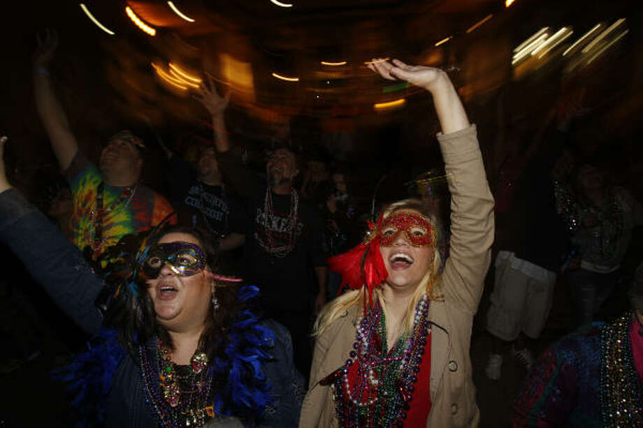 Deborah Taylor, left, of Cypress and her niece, Nicole Beldon, of Fayetteville, NC try to catch beads during the 100th celebration of Mardi Gras! Galveston along the Strand. Photo: Melissa Phillip, Houston Chronicle