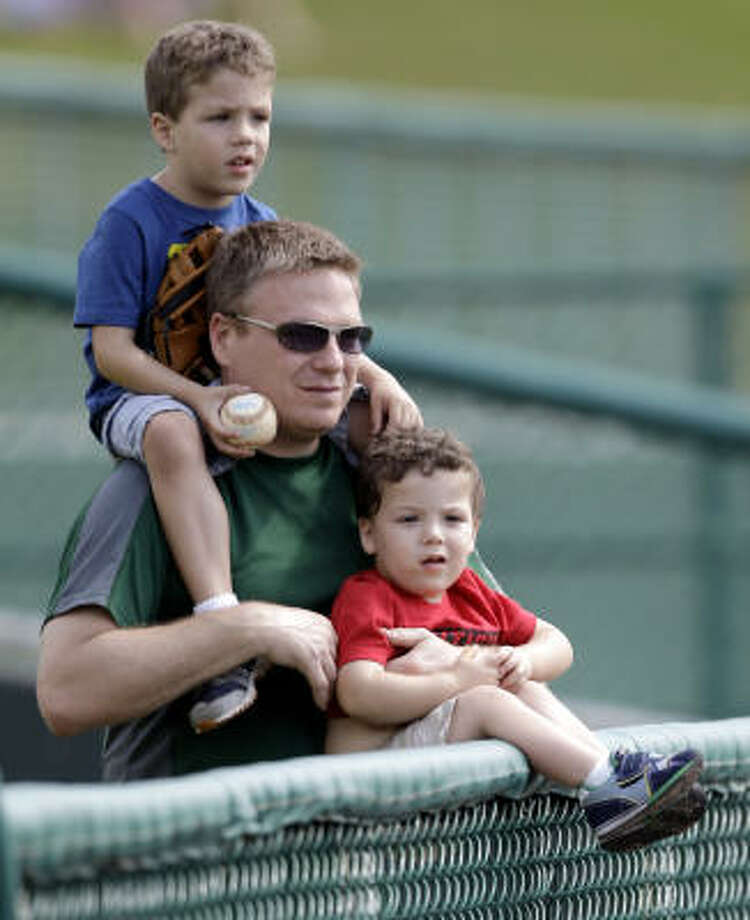 Adam Rich, center, and his sons, Andrew, left, and Nathan, right, watch the Astros take batting practice before a spring training game. Photo: David J. Phillip, AP
