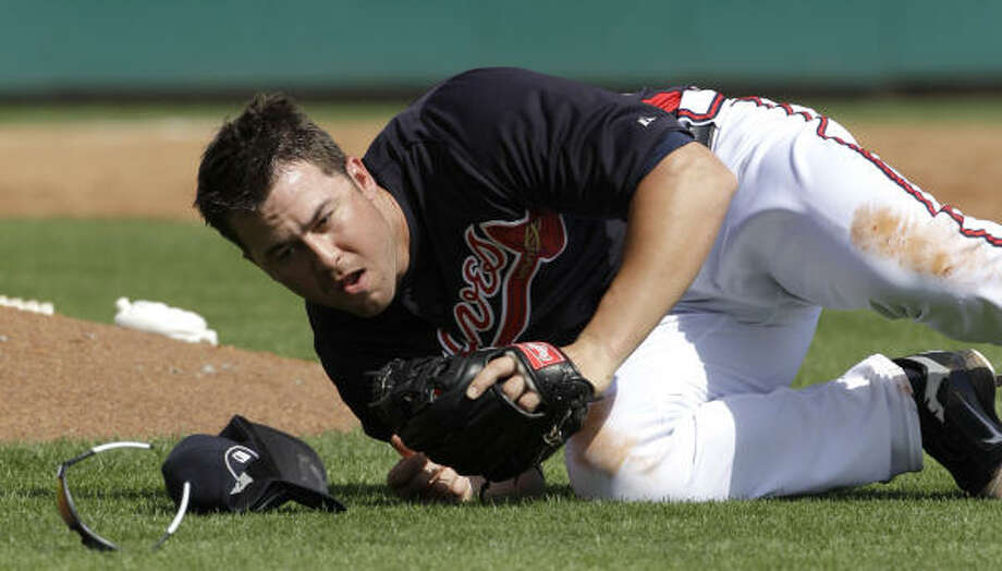 Braves third baseman Brandon Hicks falls while trying to field a pop fly hit by Astros' Carlos Lee during the third inning. Lee was safe at first on the play. Photo: David J. Phillip, AP