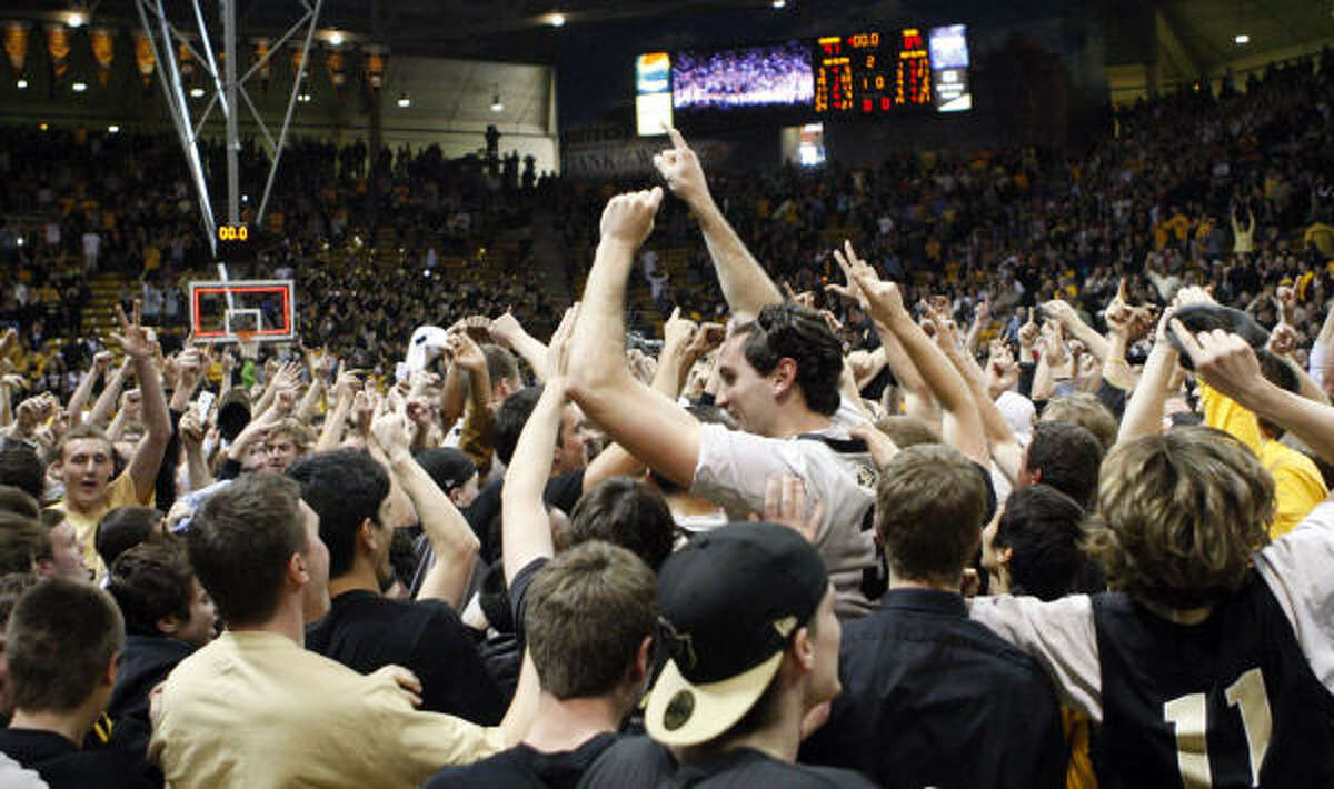 Colorado players celebrate with fans after their 91-89 victory over Texas.