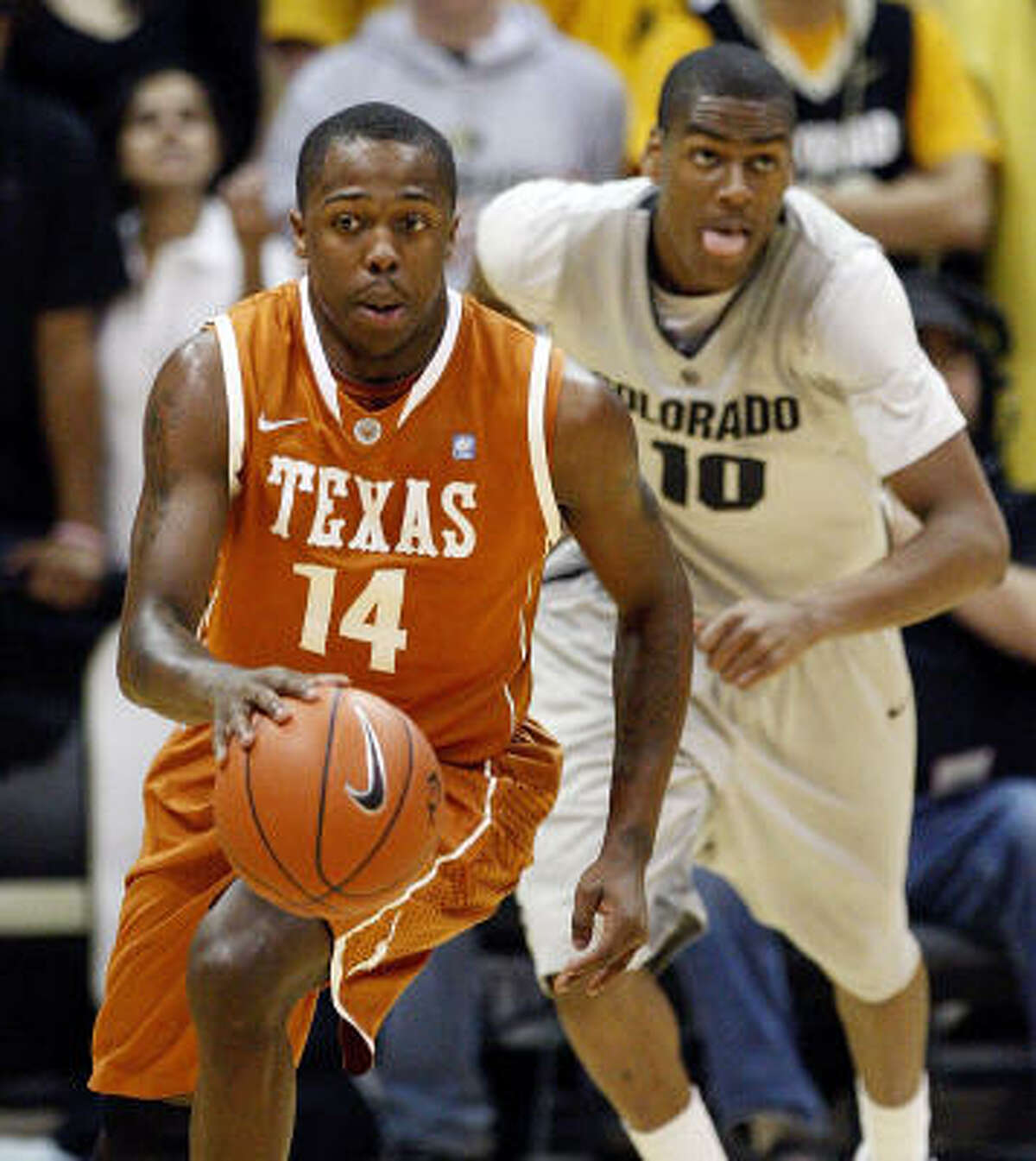 Texas guard J'Covan Brown drives the ball up court as Colorado guard Alec Burks gives chase.