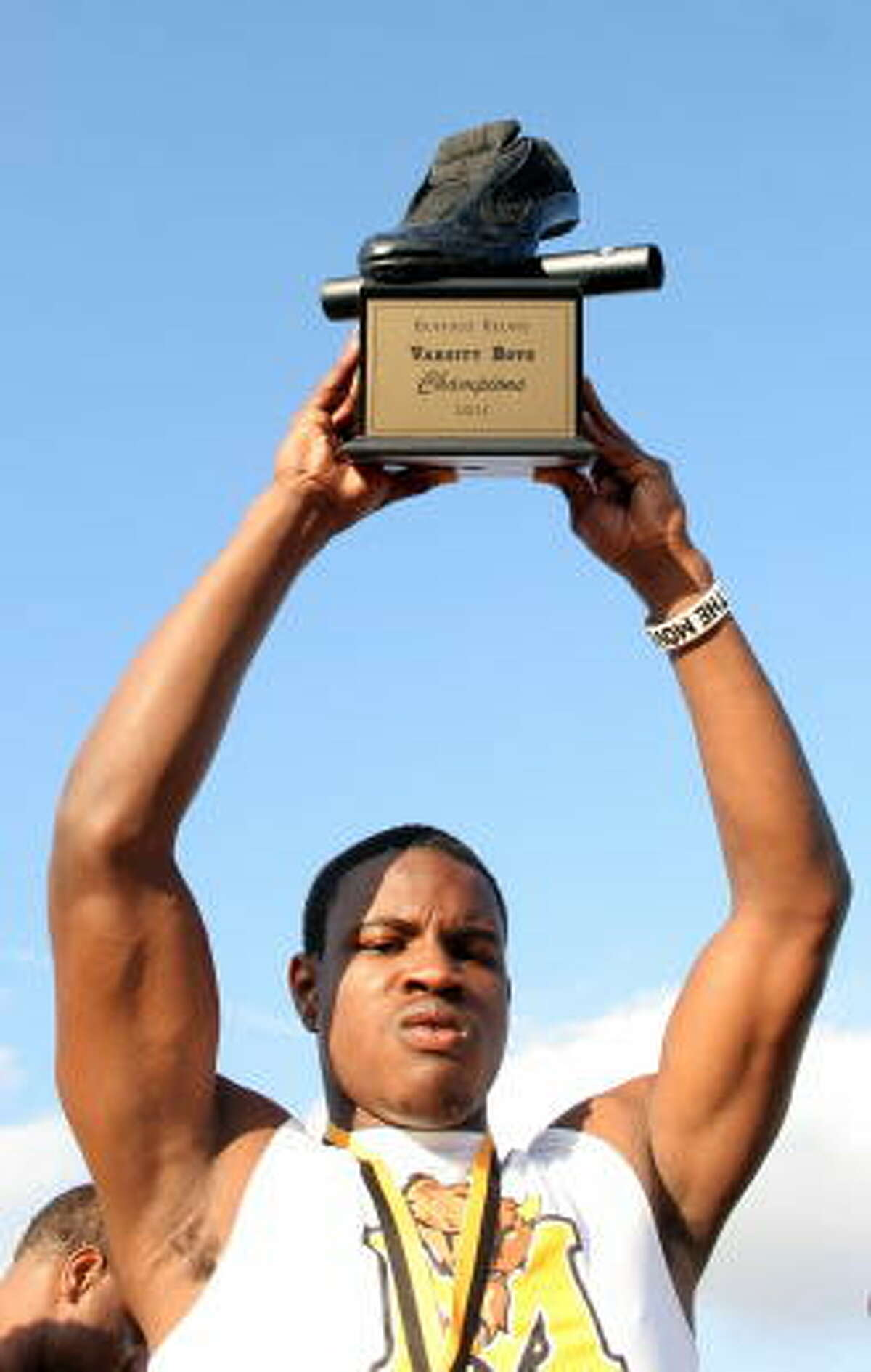 Marshall's Tylor White holds up the team title award.