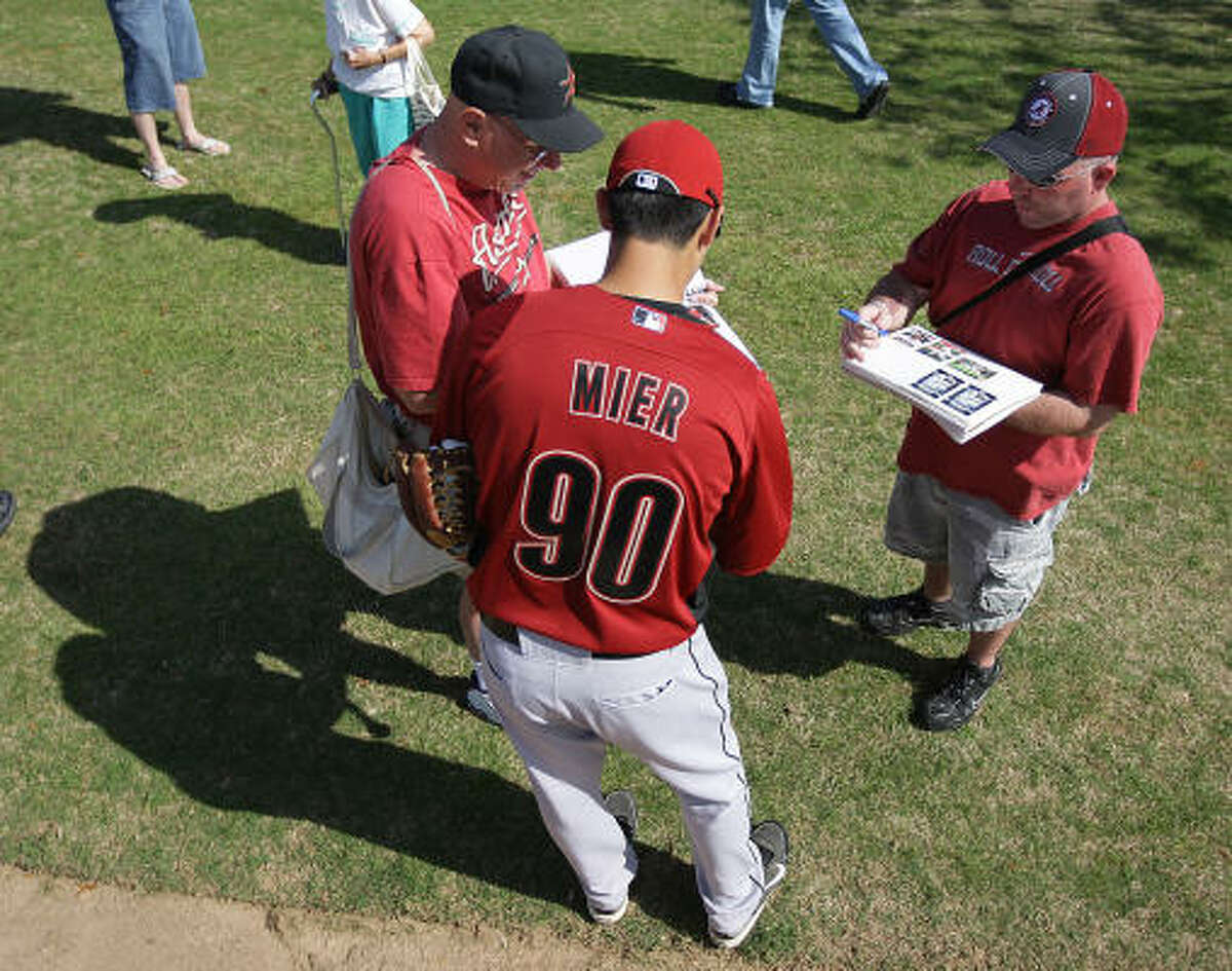 Infielder Jiovanni Mier (90) signs autographs for fans.