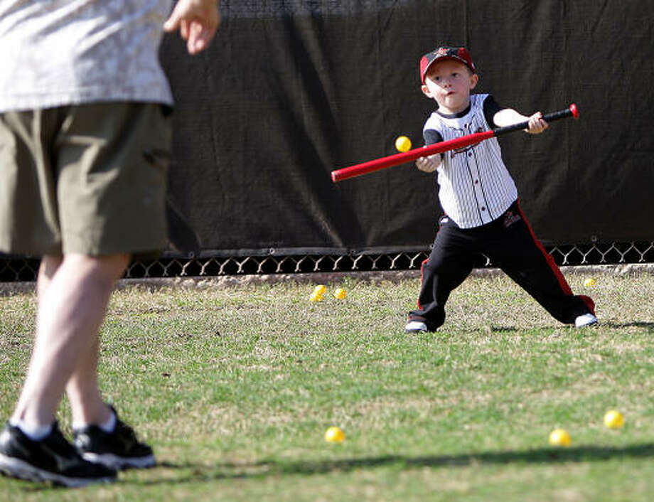 Wyatt Barmes, 3, tries to bunt a whiffle ball tossed to him by his grandfather, Dan Dennison, as they wait to watch Wyatt's father, Astros infielder Clint Barmes, practice. Photo: Karen Warren, Chronicle