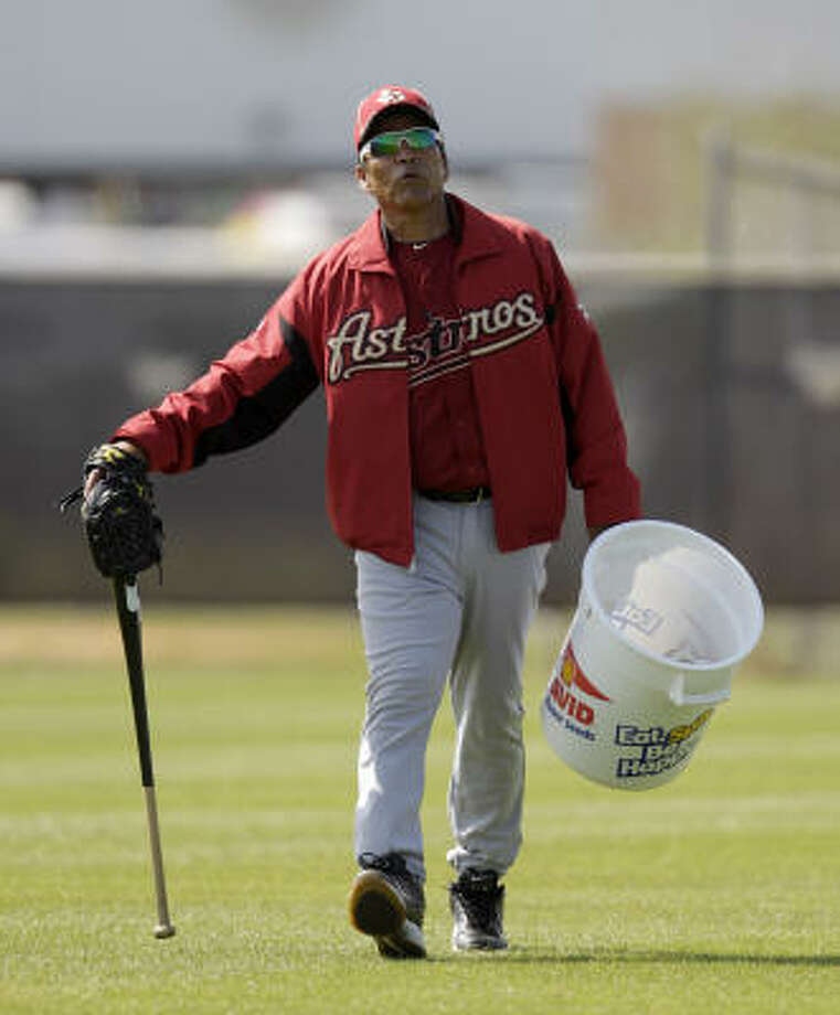 Jose Cruz carries a bucket of balls during drills. Photo: Karen Warren, Chronicle