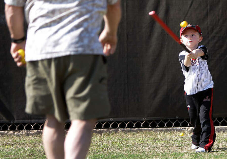 Wyatt Barmes, 3, takes a swing at a whiffle ball tossed to him by his grandfather, Dan Dennison, as they wait to watch Wyatt's father, infielder Clint Barmes, practice. Photo: Karen Warren, Chronicle