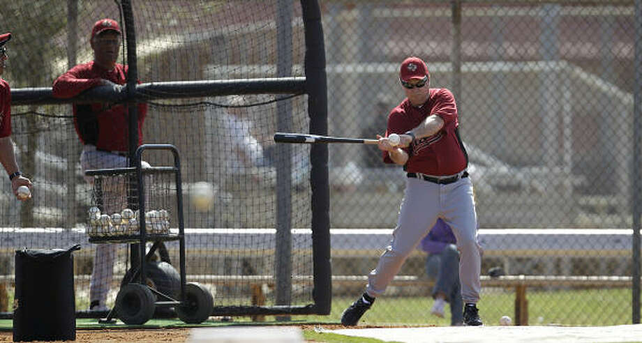 Hitting coach Mike Barnett hits a ball to first base during drills. Photo: Karen Warren, Chronicle