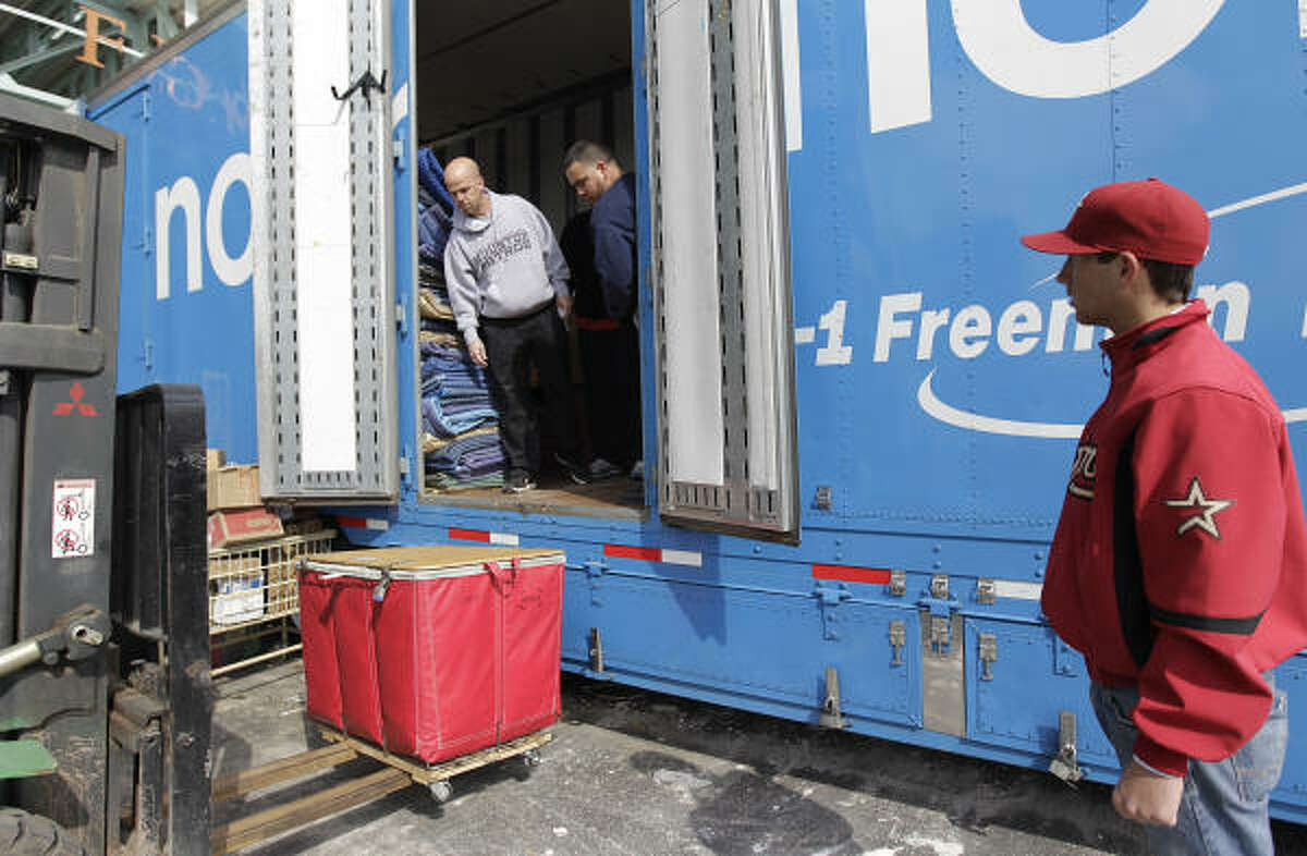 Astros equipment manager Carl Schneider (grey top) supervises as baseball equipment is loaded into a moving truck.