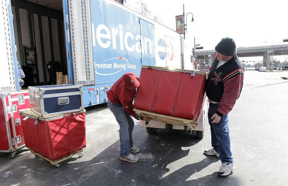 Batboy Patrick Eaves, left, and Chris Clarke work on getting some baseball equipment into the truck. Photo: Karen Warren, Chronicle