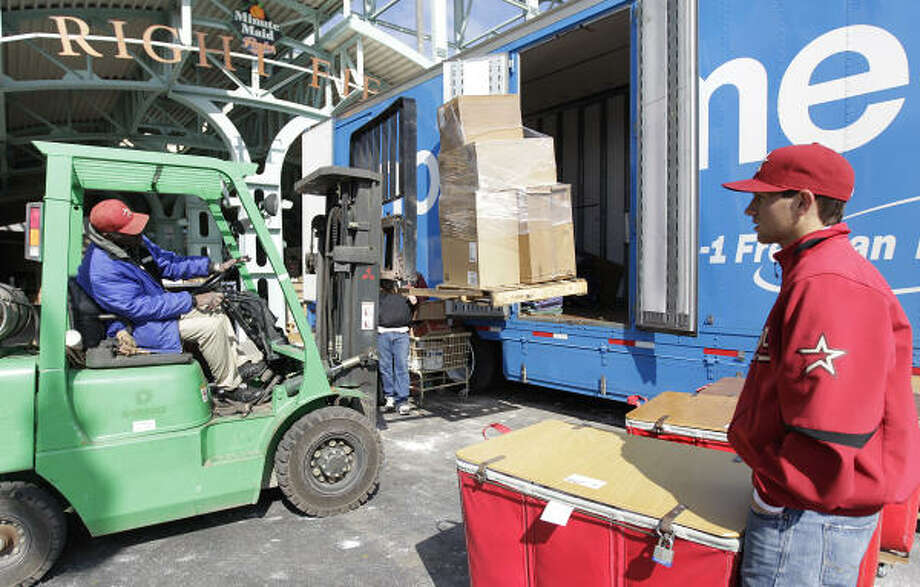 Batboy Patrick Eaves looks on as Willie Berry loads baseball equipment with a forklift. Photo: Karen Warren, Chronicle